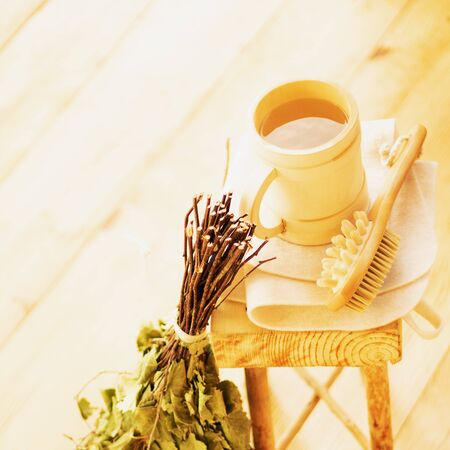 Pampering and relaxing in the sauna. Accessories for a steam room, wooden furniture, a bath broom and water in a mug.