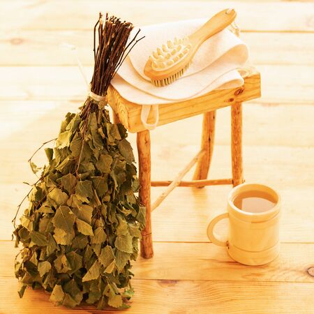 Pampering and relaxing in the sauna. Accessories for a steam room, wooden furniture, a bath broom and water in a mug. Beautiful nice color wooden interior