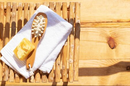 Set for a steam bath. Towel, soap and body brush. View from above. Bright sunshine and shadows. Rest and relaxation, Spa pampering.