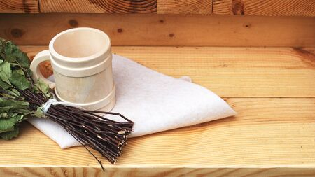 Pampering and relaxing in the sauna. Accessories for a steam room, wooden furniture, a bath broom and mug. Copy spase Banco de Imagens