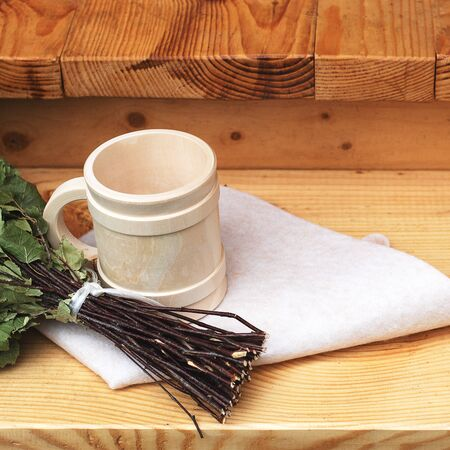 Pampering and relaxing in the sauna. Accessories for a steam room, wooden furniture, a bath broom and mug.