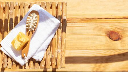 Set for a steam bath. Towel, soap and body brush. View from above. Bright sunshine and shadows. Banco de Imagens