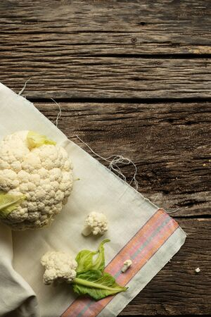 Cooking Cauliflower. Top view, wooden table, a whole head of cauliflower.