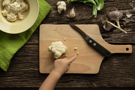 Cooking Cauliflower. Top view, wooden table. The child helps to cook Reklamní fotografie