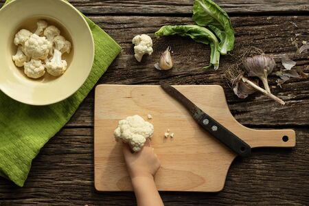 Cooking Cauliflower. Top view, wooden table. The child helps to cook food. The concept of healthy eating and love in the family Stockfoto