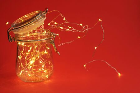 Garland inside a jar with a yoke. Red background and warm light, christmas mood. Minimalism and a classic combination of colors. New Year's greetings.
