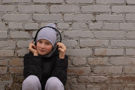 A teenager listens to music in black wireless headphones. Cool once and brick walls of houses. Modern children and technology