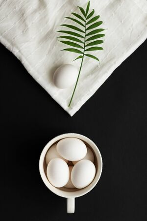 Happy easter. The eggs are in a circle. On the napkin lies one egg and a green branch of the plant. Modern design concept and black and white color scheme.