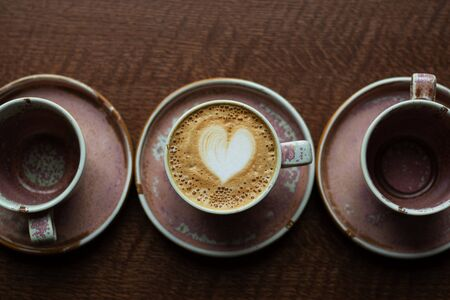 A cup of coffee in the shape of a heart with milk foam. Cappuccino among the dishes on the table. A service of one color from mugs and saucers. Top View. Stock Photo