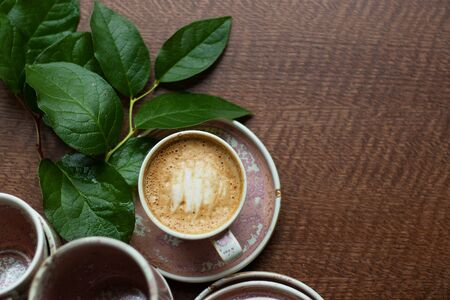 A cup of coffee with milk foam. Cappuccino stands among other dishes of the same color on the table. A branch of greenery decorates the composition. Homeliness and pleasant atmosphere. Top View.