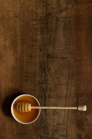 Honey in a bowl with a spoon on a warm color wooden table. Useful sugar substitute Banque d'images