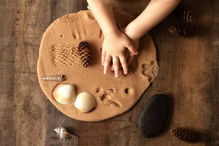 Children play with salt dough on the kitchen table. Hands mold clay with their own hands to create homemade zero-waist toys. Creative lesson with a test of natural products. Development of children in the period of self-isolation.