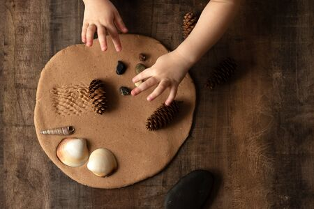 Modeling with salt dough on the kitchen table. Natural materials for the game, the natural composition of the product. Creative development of children in the period of self-isolation. Imagens