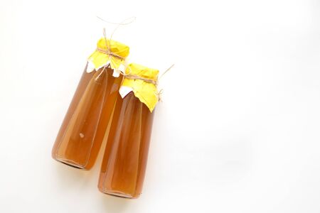 Refreshing filtered kombucha tea in a glass bottle. Fermented healthy drink for two, tied with yellow paper and twine
