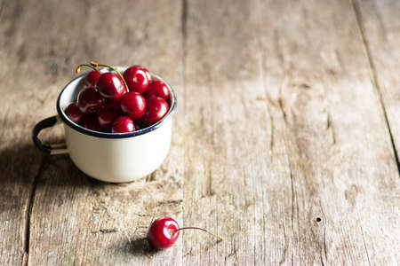 Ripe fresh sweet cherry lies in an old metal mug on a wooden table. Sweet wholesome dessert. Environmental design and minimalism.