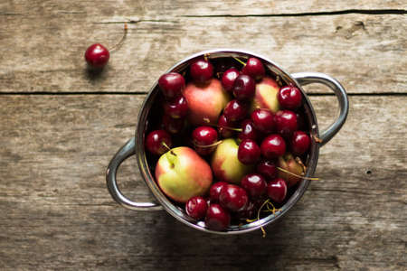 Sweet cherries and nectarines lie in a metal pan on a wooden table. Conservation for the winter.