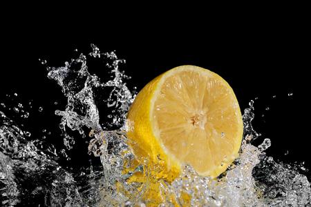 Fresh lemon falling into water. Isolated on black background