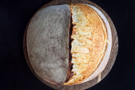 Sourdough bread on wooden cut board on black background 版權商用圖片 - 148558171