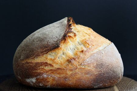 Sourdough bread on wooden cut board on black background