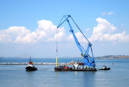 towed: Floating crane and marine tug in the port of Russia Stock Photo