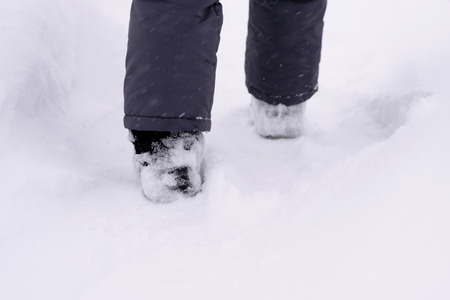 trample: childs feet in the snow shoe walking on a track in a snowstorm.