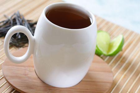 Photo of a tea mug with a wooden saucer and a lemon