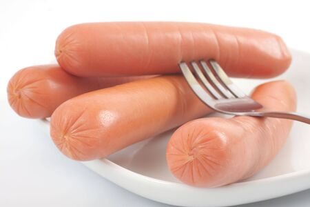 Fresh sausages on a plate. Studio isolated