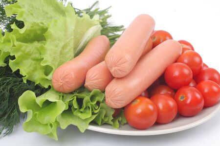 Fresh sausages on a plate with with tomatoes and lettuce