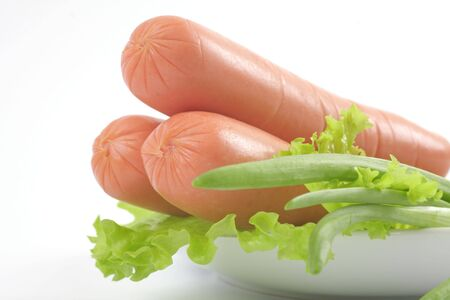 Fresh sausages on a plate with vegetables. Objects over white.