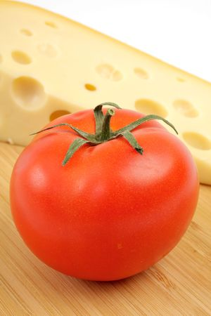 Cheese and tomato on a wooden board. Studio isolated photo