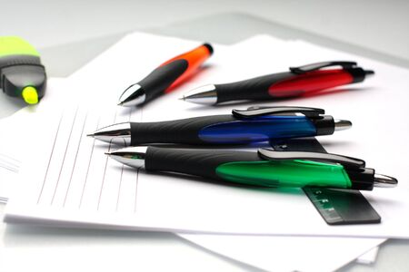 Some pens lie on a white paper