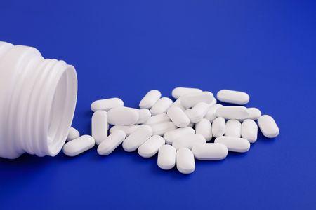 Spilled tablets and medicine bottle.Tablets on a blue background Stock Photo - 6837184