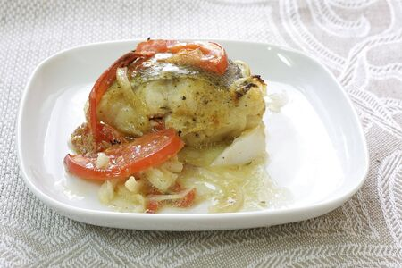 Fish with a tomato and an onions on a white plate Stock Photo
