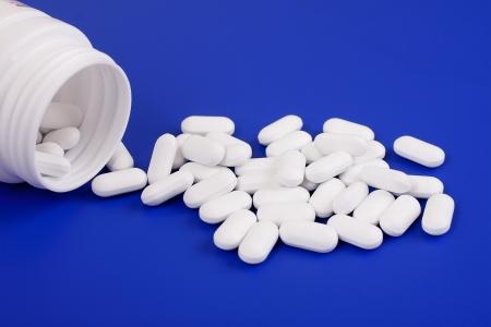 Spilled tablets and medicine bottle.Tablets on a blue background
