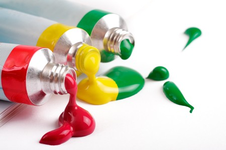 red, yellow and green colors in tubes on a white background photo