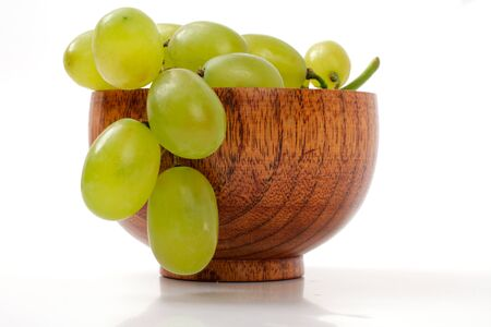 Grapes in a wooden cup, over white, studio isolated
