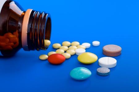 Spilled tablets and medicine bottle  Tablets on a blue background Stock Photo - 13232123