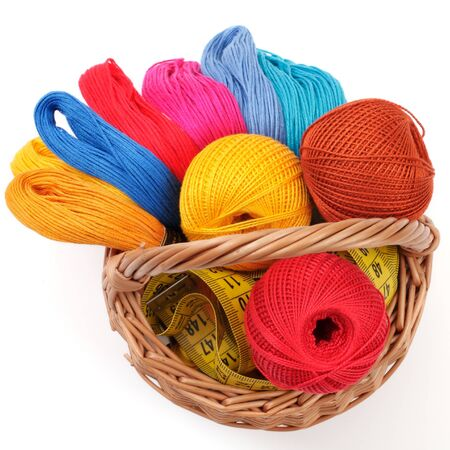 colored threads for needlework in the basket, over white photo