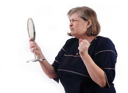 cerveza negra: la robusta mujer de mediana edad grit�, mirando en un espejo Foto de archivo
