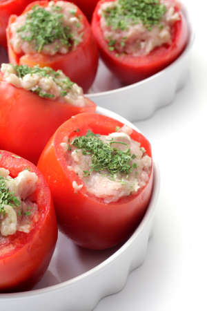 Cooking tomatoes stuffed with chicken meat in a white mold Stock Photo