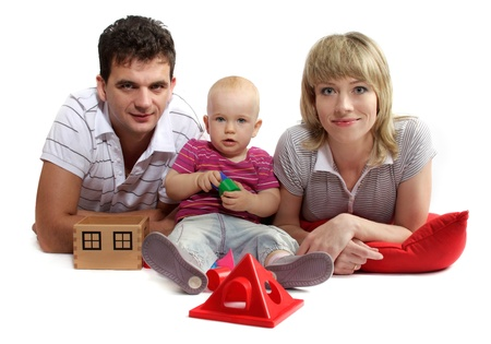 happy young family lying on the floor on red cushions, white background, studio isolated photo