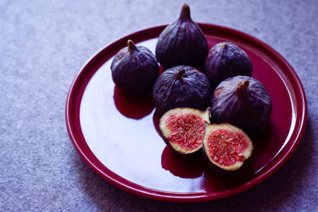 brightly cut figs from turkey on a burgundy plate