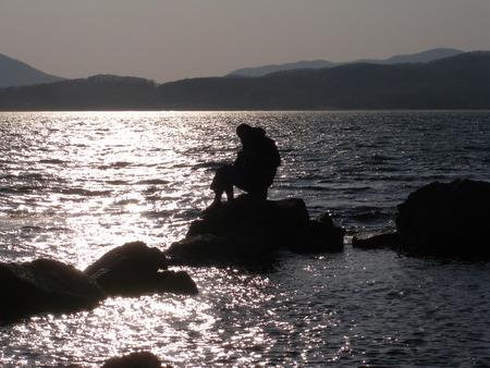 Silhouette of sitting man, sea sunset photo