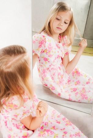 blonde little girl: Little girl looking at mirror, studio portrait
