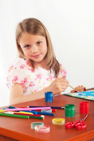 Smiling little girl drawing picture, paints, hobby photo