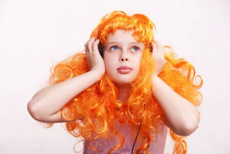periwig: Beautiful little redheaded girl  child listening to disco music with headphones against white background Stock Photo