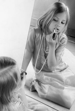 Little girl rouge lips and looking at mirror, black and white portrait photo