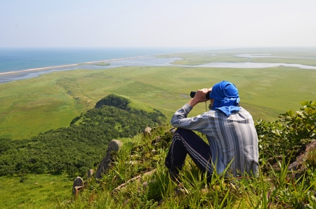 Man looking in binoculars, the border of Russia with North Korea photo