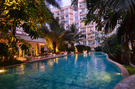 Swimming pool on condominium area, illuminated water in evening, resort, Pattaya, Thailand