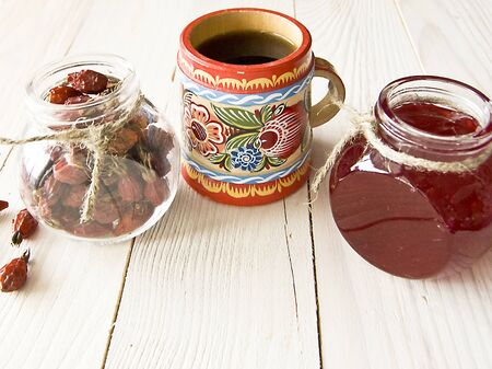 cold cure: Hot tea in a wooden mug with a pattern, raspberry jam Stock Photo